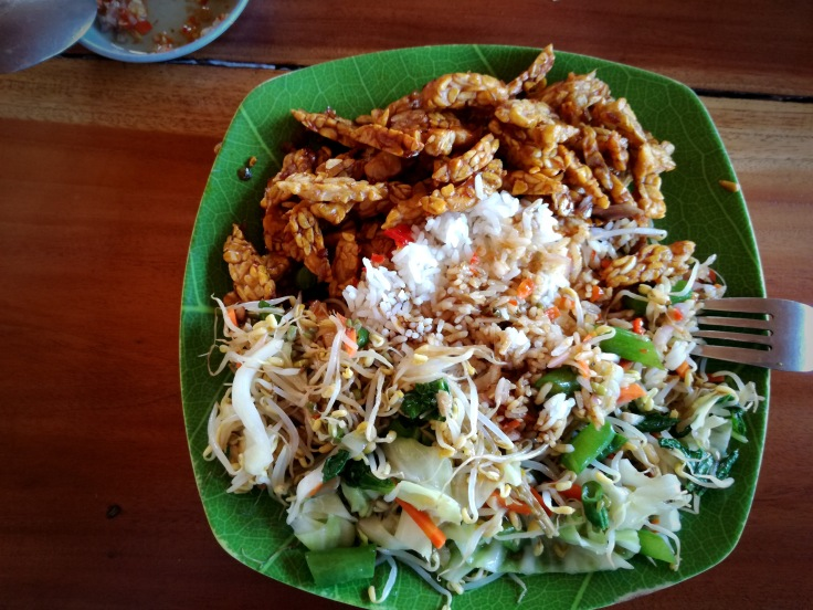 Nasi campur with fried tempeh and portion of salad with delicious sprouts.